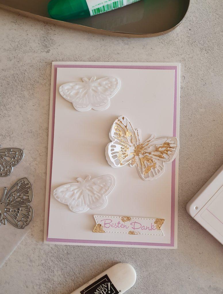 Eine Karte in Weiß und Freesienlila. Auf der Karte sind 3 Schmetterlinge, davon ist einer mit Gold verziehrt. Und ein Banner mit  Besten Dank.