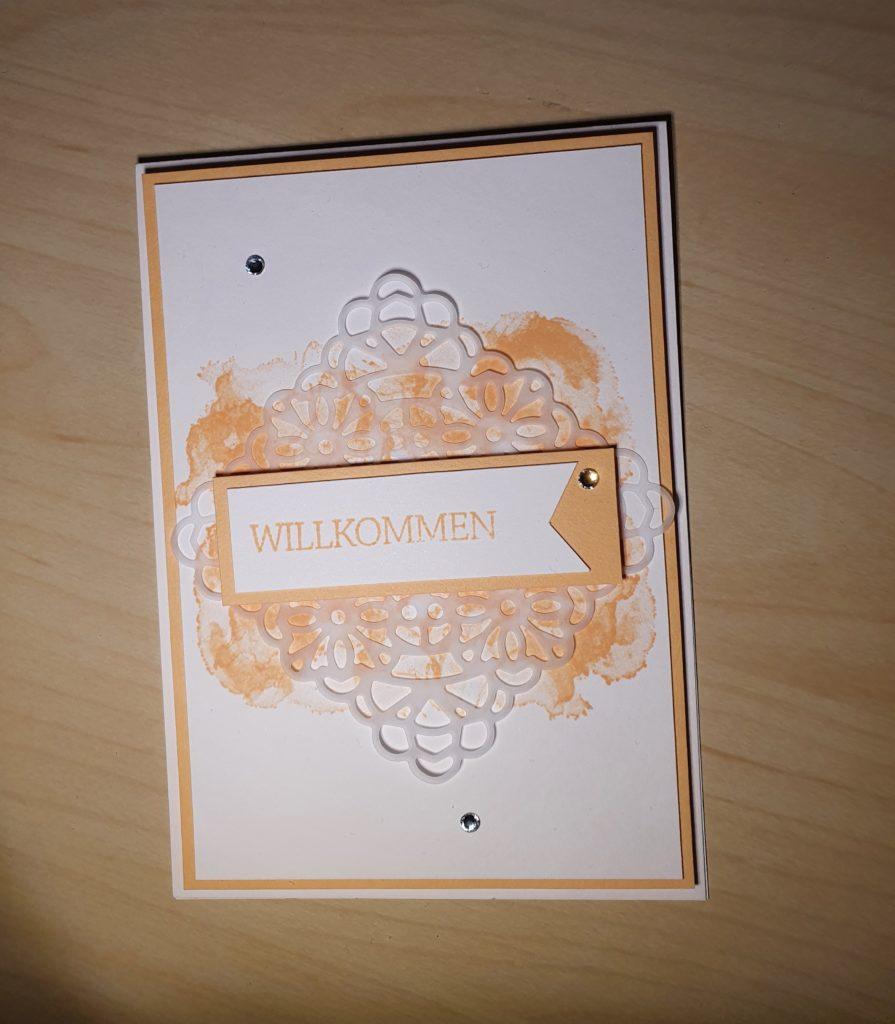 BlogHop Team Stempelpalast 31.05.2021 Eine Karte in Papaya ud Grundweiß mit einem Willkommen Stempel abdruck auf der Vorderseite. Es sind drei Glitzersteine angeordnet.