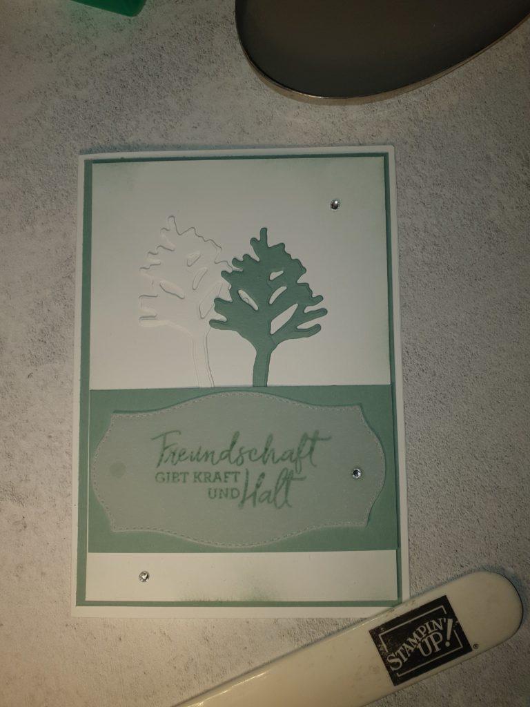 """Zum BlogHop Happy Friday 18.06.2021 habe ich eine in Grundweiß mit einem Aufleger in Seladon. Auf dem zweiten Aufleger in Grundweiß sind zwei Bäume aufgestanzt in Seladon und Grundweiß. Auf den Baäumen ist ein Spruch auf Permantentpapier gestempelt """"Freundschaft gibt Kraft und Halt"""" und auf der Karte sind drei Glitzersteine zu sehen."""