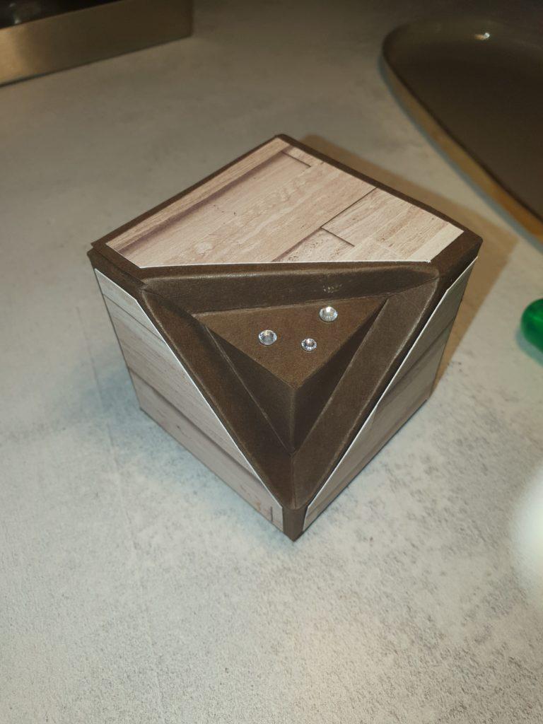 BlogHop Team Stempelpalast Juni 2021 Thema Besondere Verpackung. Man sieht eine  Box mit Ecke in Espresso und Desingerpapier das aussieht wie Holzbretter.